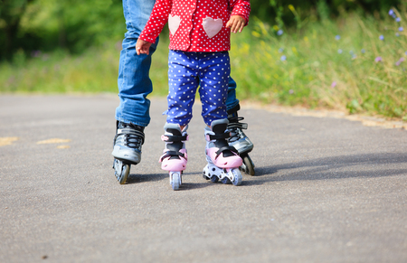 daugther: father teaching little daugther to roller skate in summer Stock Photo