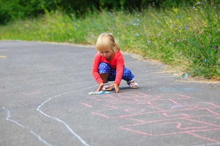 hopscotch: little girl drawing hopscotch on playground outdoors
