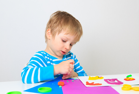 little dough: little boy playing with clay dough, education and daycare concept
