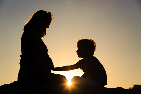 Silhouette of little boy touching pregnant mother tummy at sunset