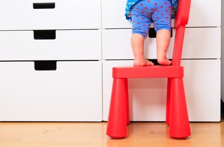baby chair: kids safety concept- little girl climbing on baby chair