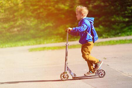 Felice piccolo ragazzo riding scooter, attivo sport per bambini