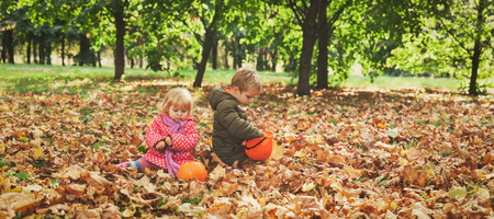 siblings: little boy and girl play with autumn leaves in nature, kids trick or treating
