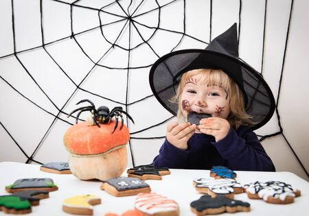 trick or treating: cute little girl eating cookies on halloween, kids trick or treating
