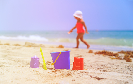 kids toys and little girl playing on the beach, kids beach activities