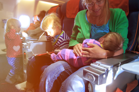 mother with newborn baby, little son and daughter travel by plane, family tourism Imagens
