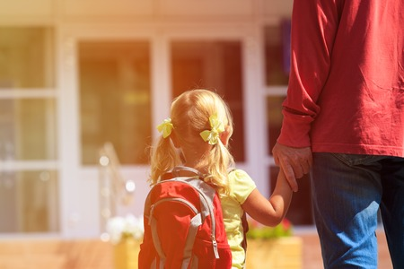 father walking little daughter to school or daycare, back to school Foto de archivo