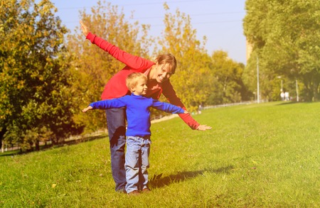 ouside: mother and son play in autumn nature, family fun