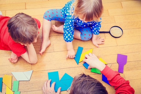 teacher and kids playing with geometric shapes, early learning concept