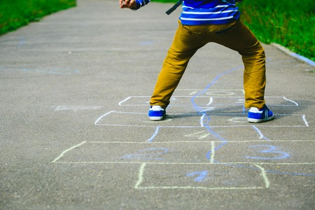 hopscotch: little boy playing hopscotch on playground outdoors, kids activities Stock Photo