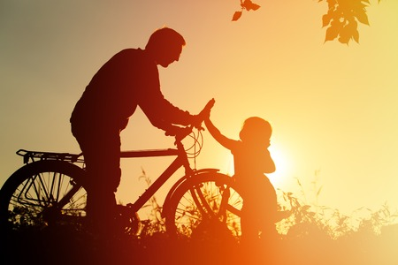 father and little daughter having fun riding bike at sunset, active family sport
