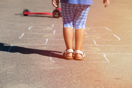 hopscotch: little girl playing hopscotch on playground outdoors