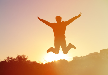 éxtasis: Silhouette of man jumping at sunset sky, happiness and success