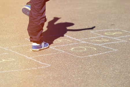 hopscotch: kid playing hopscotch on playground, children outdoor activities