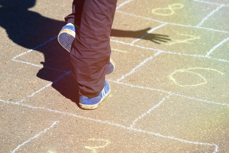 hopscotch: kid playing hopscotch on playground, kids outdoor activities Stock Photo
