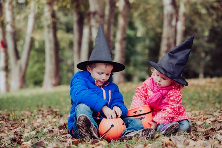 trick or treating: little boy and girl in halloween costume play at autumn, kids trick or treating