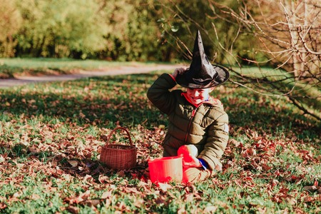 trick or treating: little boy in halloween costume in autumn, kids trick or treating