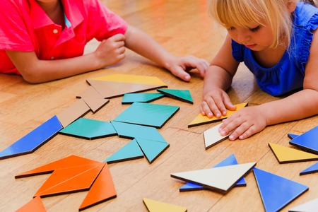 solves: kids learning -little boy and girl playing with geometric shapes or puzzle Stock Photo