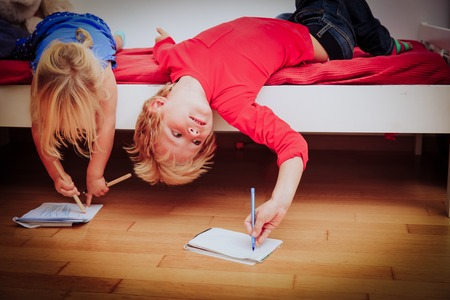 pretend: kids pretend doing homework at home by fooling around Stock Photo