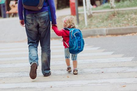 Gehende kleine Tochter des Vaters mit Rucksack zur Schule oder zur Kindertagesstätte Standard-Bild - 63779139