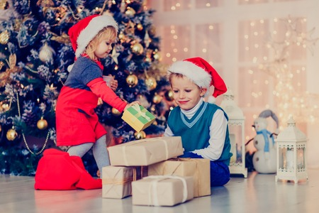 kids opening christmas presents in decorated living room christmas and new year stock photo