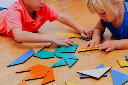 kids learning -little boy and girl playing with geometric shapes or making puzzle