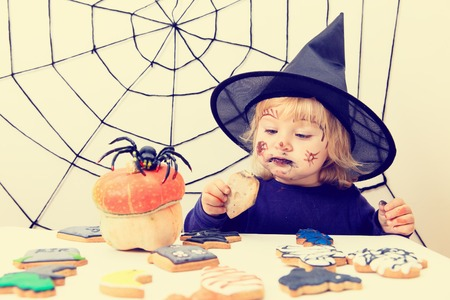 little girl eating cookies on halloween, kids trick or treating Stock Photo