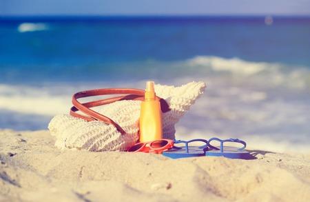 suncream: vacation concept - bag, suncream, glasses and flip flops on the beach