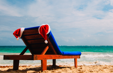 chair lounge with red Santa hats on tropical summer beach