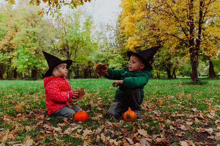 treating: kids in halloween costume play at autumn nature, kids trick or treating