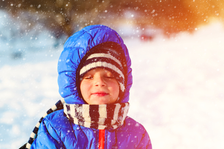 little boy enjoy snow in winter nature, kids winter activities Stock Photo