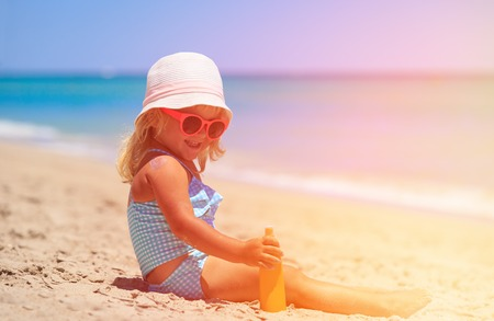 little girl applying sunblock cream on shoulder, sun protection