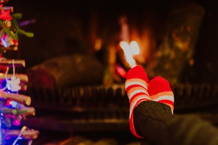 cosiness: Woman feet in wool socks warming by fireplace, winter holidays concept