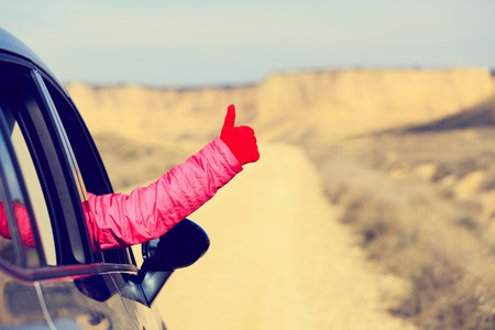 road to love: Woman hand with thumb up travel by car on road, love travel concept