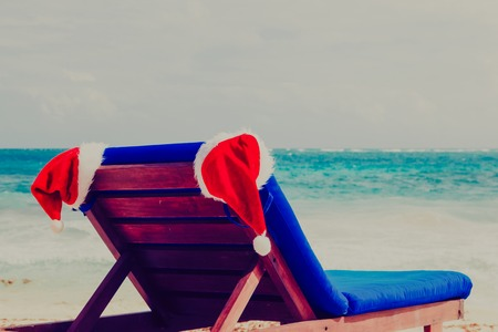 bahamas celebration: chair lounge with red Santa hats on tropical beach, Christmas at beach Stock Photo