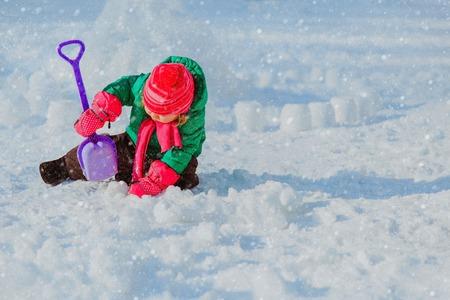 dig: little girl dig in winter snow, kids winter fun Stock Photo