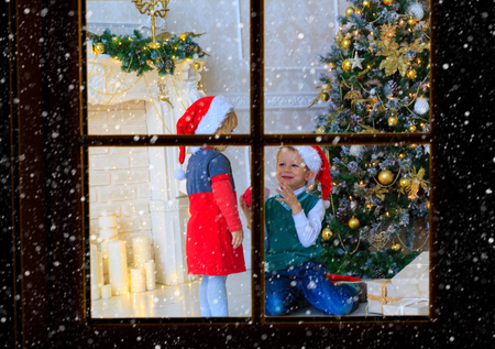 kids opening christmas presents in decorated living room viewed through window from outside christmas celebration - Outdoor Christmas Presents Decorations