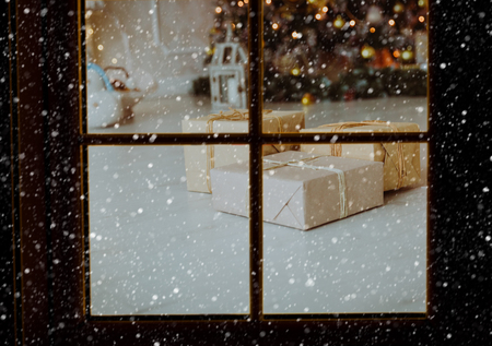 Christmas presents in decorated room viewed through window from outside, Christmas celebration Foto de archivo