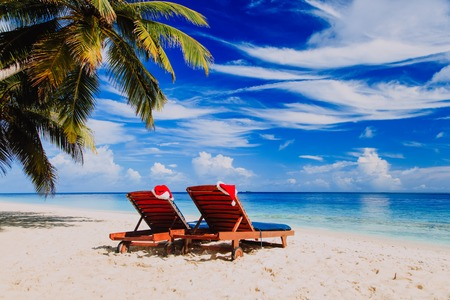 Christmas at beach -two chair lounges with Santa hats at sea
