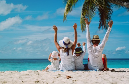 happy family with two kids hands up on the beach, family beach vacation Foto de archivo