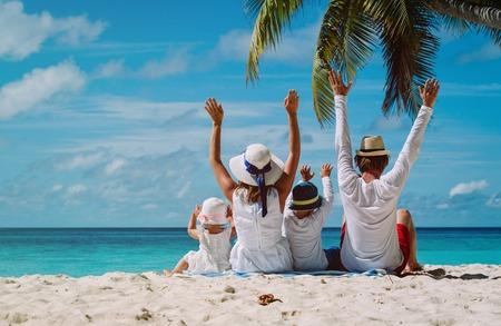 gelukkig gezin met twee kinderen handen omhoog op het strand, familie strandvakantie