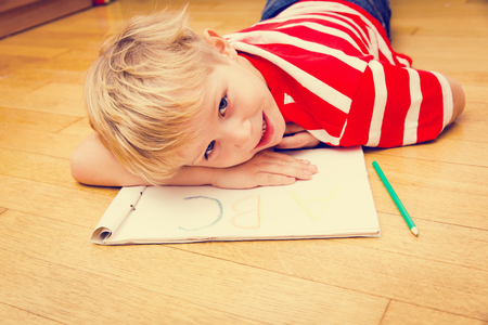 learning by doing: little boy writing letters, doing homework- kids learning and education