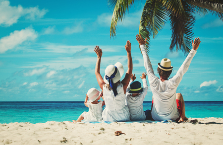 summer holiday: happy family with two kids hands up on the beach