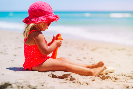 suncream: sun protection concept - little girl with suncream at tropical beach