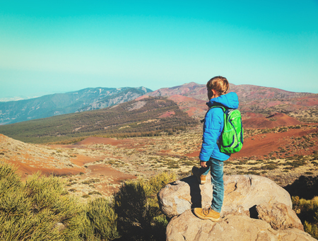 little boy hiking in mountains looking at beautiful landscape Stock Photo