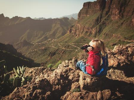 Kleines mädchen wandern in den bergen auf dem fernglas suchen