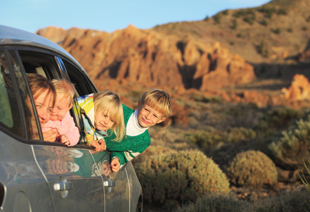 family travel by car- happy mother with tree kids in mountains