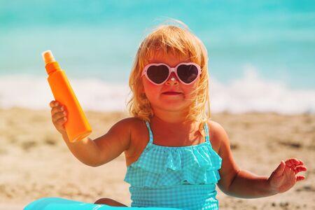 suncream: sun protection concept - little girl with suncream at beach