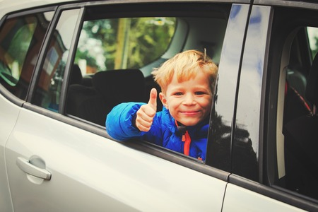 happy little boy loves to travel by car