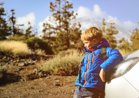 little boy with backpack travel by car in nature